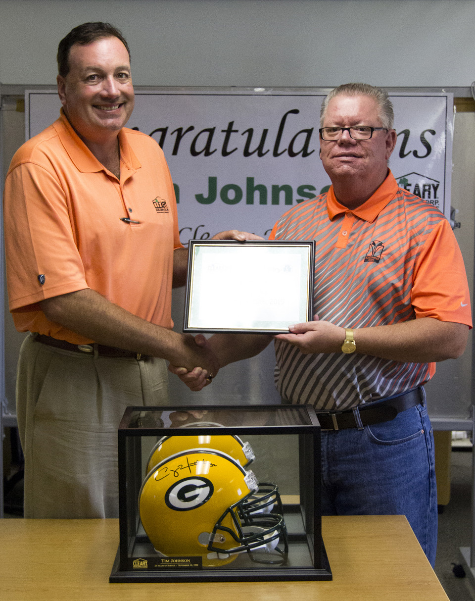 Tim Johnson (right) is presented with a Clay Matthew's signed Packers helmet by Sean Cleary (left) in recognition of 25 years of service with Cleary Building Corp.